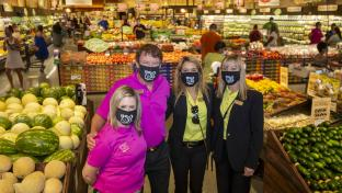 a group of people standing in a store filled with lots of produce